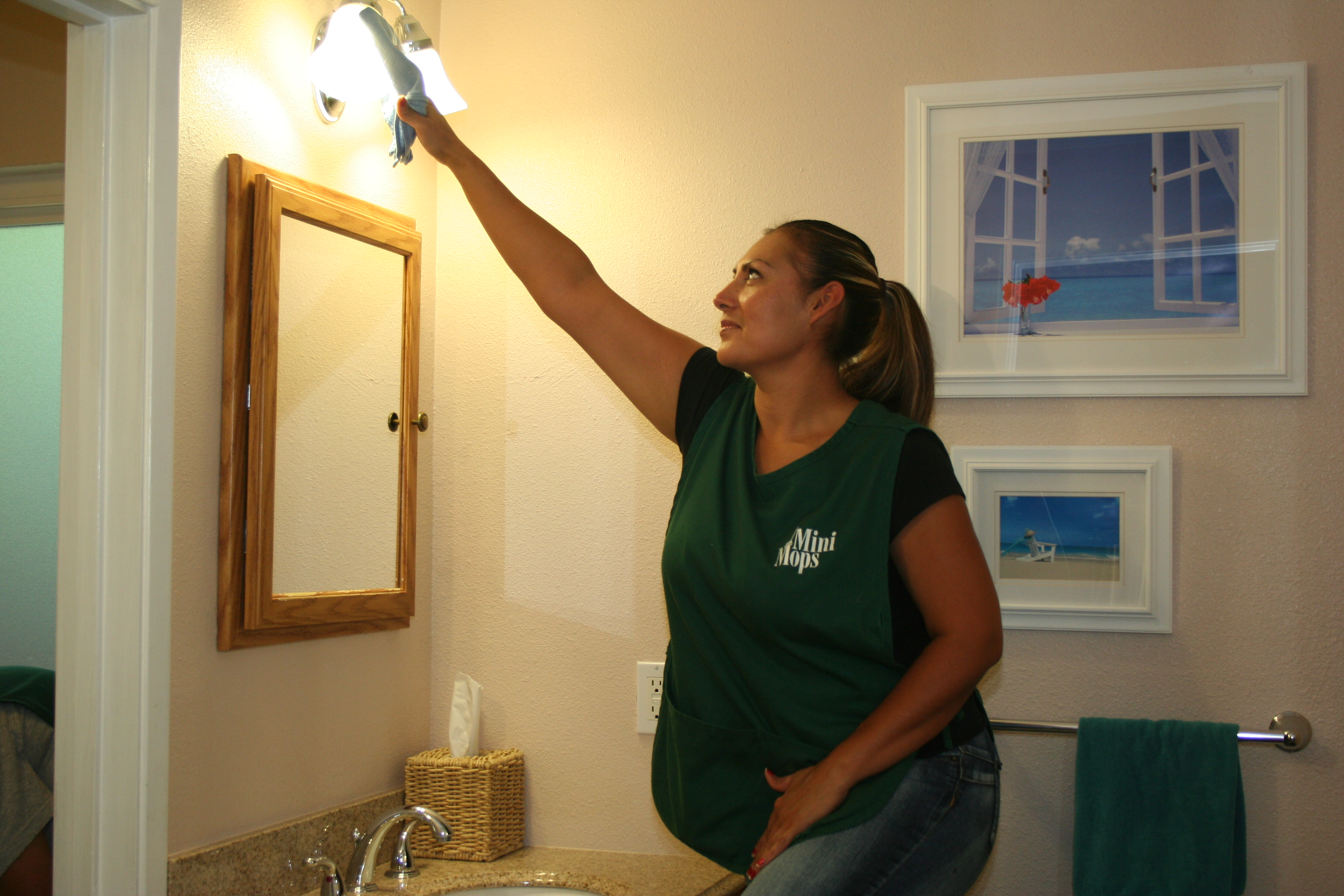 Mini Mops House Cleaning team member cleaning bathroom light fixtures