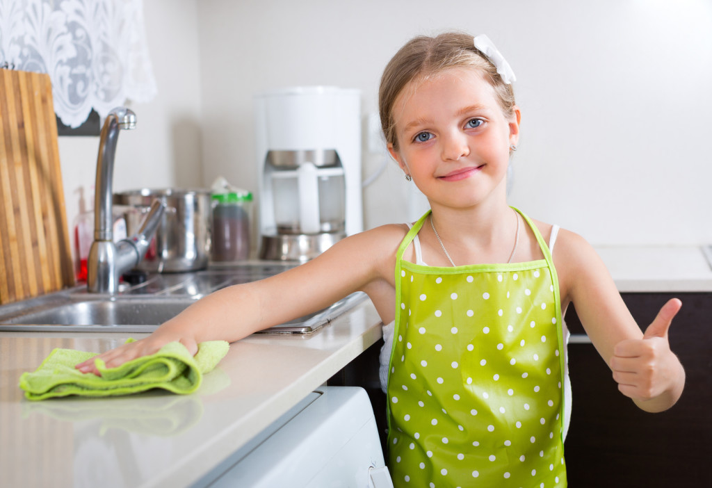 household chores for kids - girl wiping kitchen counter